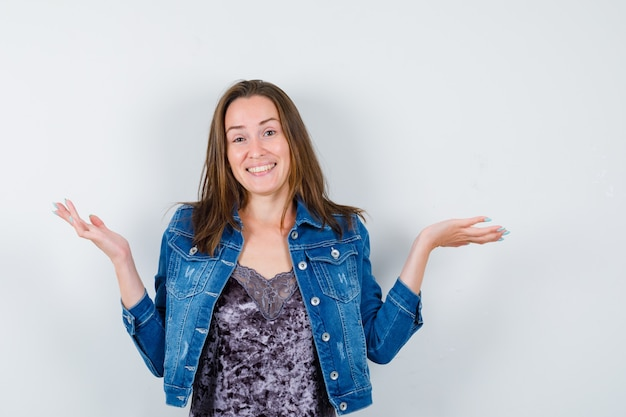 Junge dame breitet handflächen in bluse, jeansjacke und sieht glücklich aus. vorderansicht.