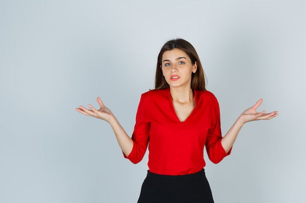 Junge dame breitet palmen in ahnungsloser geste in roter bluse, rock und hilflos aussehend aus