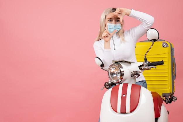 Junge dame der vorderansicht auf moped mit gelbem koffer, der kamerazeichen macht