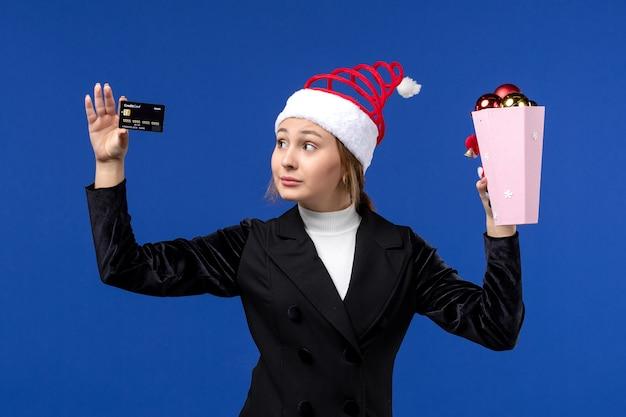 Junge dame der vorderansicht, die bankkarte auf neujahrs-emotionsfeiertagsspielzeug der blauen wand hält