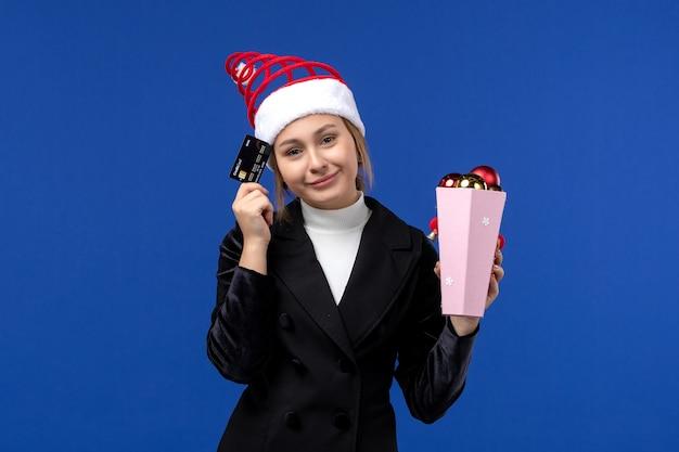 Junge dame der vorderansicht, die bankkarte auf neujahrsgefühl-feiertagsspielzeug der blauen wand hält