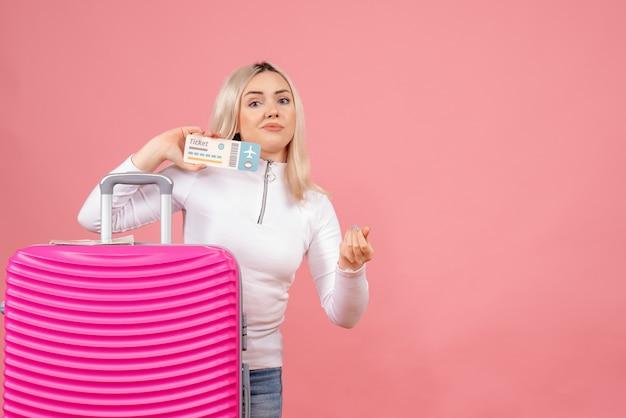 Junge dame der vorderansicht, die hinter rosa koffer steht, der flugticket hält