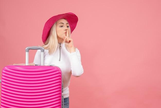 Junge dame der vorderansicht, die hinter rosa koffer steht, der shh zeichen macht