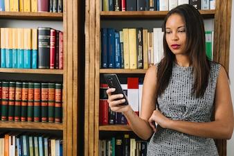 Junge Dame des Afroamerikaners, der Smartphone nahe Büchern verwendet