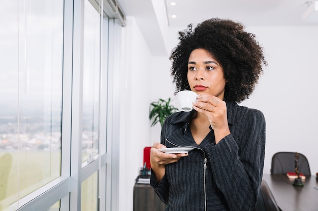Junge dame des afroamerikaners mit cup nahe fenster