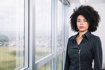 Junge Dame des Afroamerikaners nahe Fenster