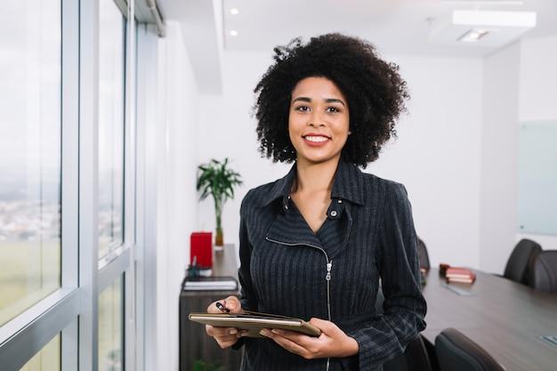 Junge dame des glücklichen afroamerikaners mit dokumenten nahe fenster