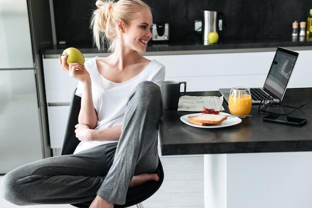 Junge dame, die apfel isst und laptop in der küche verwendet