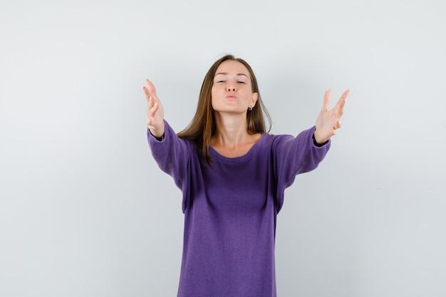 Junge dame, die arme für umarmung und kuss in der vorderansicht des violetten hemdes öffnet.