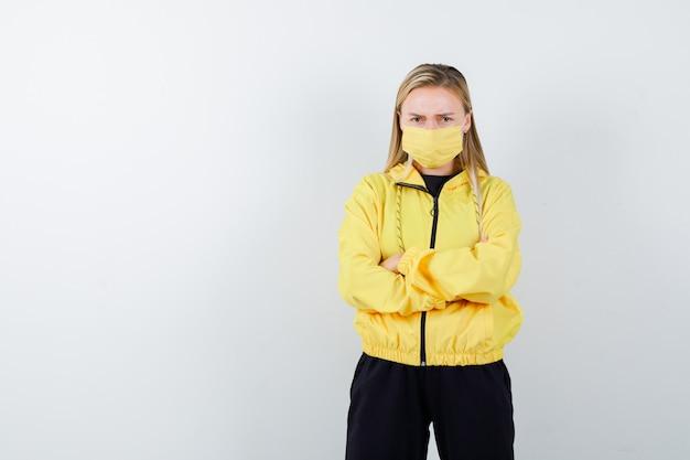 Junge dame, die arme im trainingsanzug, in der maske gefaltet hält und nervös schaut, vorderansicht.