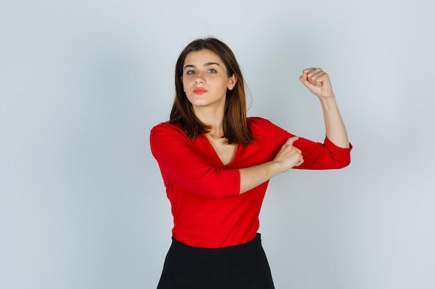 Junge dame, die armmuskeln in roter bluse, rock zeigt und selbstbewusst aussieht