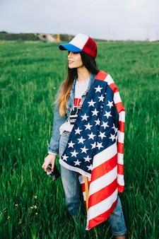 Junge dame, die auf dem gebiet mit amerikanischer flagge bleibt