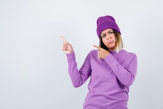 Junge dame, die auf die obere linke ecke in lila pullover, mütze zeigt und enttäuscht aussieht, vorderansicht.