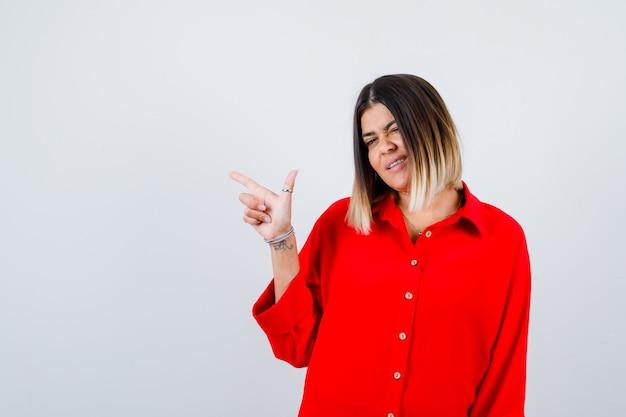 Junge dame, die auf die obere linke ecke in rotem übergroßem hemd zeigt und selbstbewusst aussieht, vorderansicht.