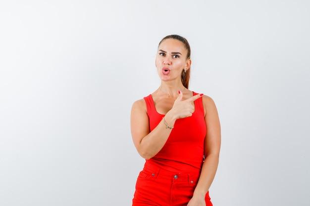 Junge dame, die auf die obere rechte ecke im roten unterhemd, in der roten hose zeigt und ratlos schaut, vorderansicht.