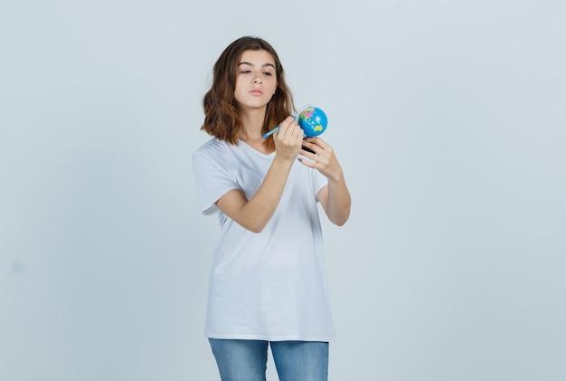 Junge dame, die auf globus mit bleistift schreibt, während in t-shirt, jeans gehalten und konzentriert schaut. vorderansicht.