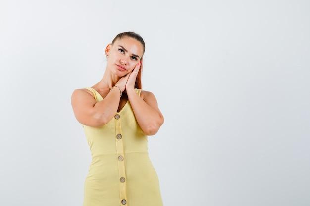 Junge dame, die auf handflächen als kissen im gelben kleid stützt und nachdenklich, vorderansicht schaut.