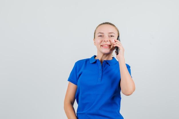 Junge dame, die auf handy im blauen t-shirt spricht und fröhlich schaut