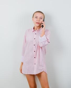 Junge dame, die auf handy in rosa hemd spricht und optimistisch schaut
