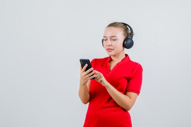 Junge dame, die auf handy in rotem t-shirt, kopfhörer tippt und froh aussieht