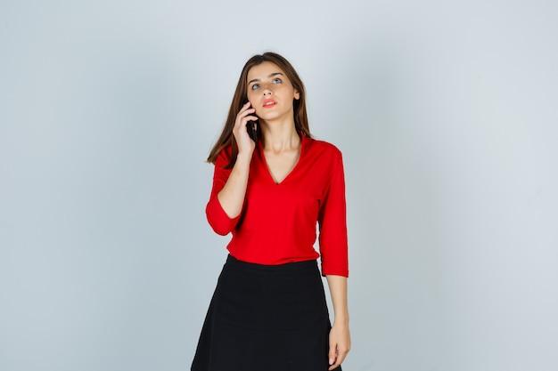Junge dame, die auf handy in roter bluse, rock spricht und nachdenklich aussieht