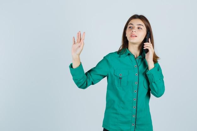 Junge dame, die auf handy spricht, stoppgeste in grünem hemd zeigt und zuversichtlich schaut. vorderansicht.