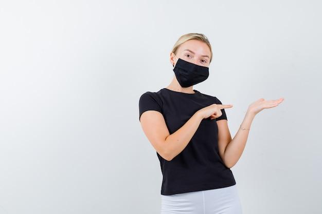 Junge dame, die auf ihre handfläche zeigt, breitete sich in schwarzem t-shirt, maske aus und sah selbstbewusst aus, vorderansicht.