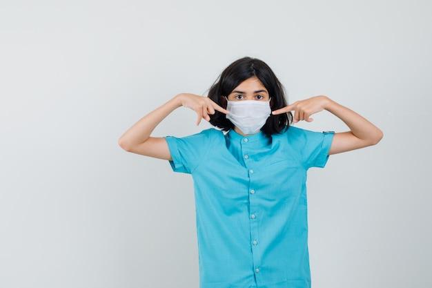 Junge dame, die auf ihre maske im blauen hemd, in der maske zeigt und selbstbewusst aussieht.