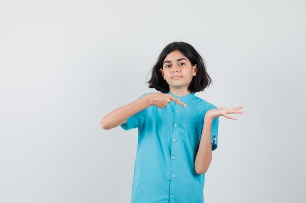 Junge dame, die auf ihre offene handfläche im blauen hemd zeigt und erfreut aussieht.