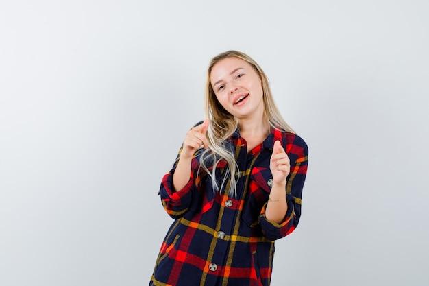 Junge dame, die auf kamera im karierten hemd zeigt und energisch, vorderansicht schaut.