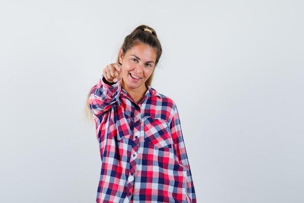 Junge dame, die auf kamera im karierten hemd zeigt und verspielte vorderansicht schaut.