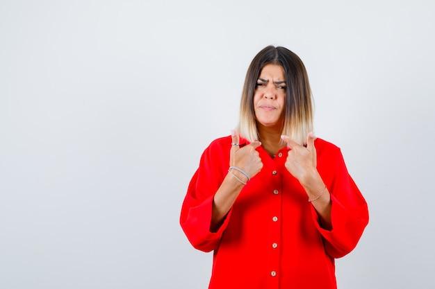 Junge dame, die auf sich selbst zeigt, um eine frage im roten übergroßen hemd zu stellen und ernst zu schauen, vorderansicht.