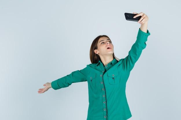 Junge dame, die aufwirft, während selfie auf handy in grünem hemd nimmt und glücklich, vorderansicht schaut.