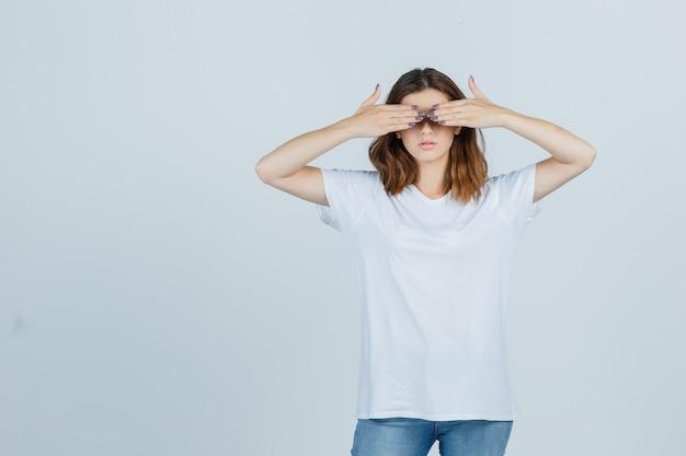 Junge dame, die augen mit händen im t-shirt, in den jeans bedeckt und selbstbewusst aussieht. vorderansicht.