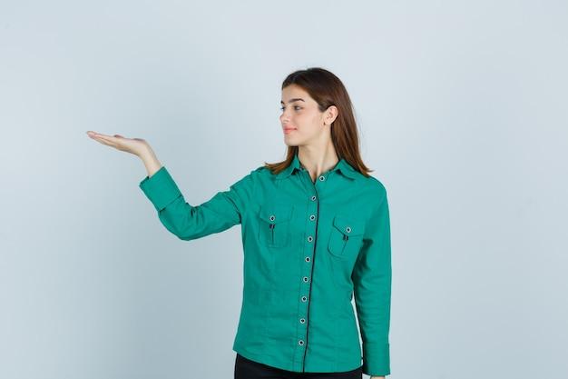 Junge dame, die begrüßungsgeste im grünen hemd zeigt und fröhlich, vorderansicht schaut.