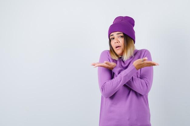 Junge dame, die beide seiten in lila pullover, mütze zeigt und verwirrt aussieht. vorderansicht.