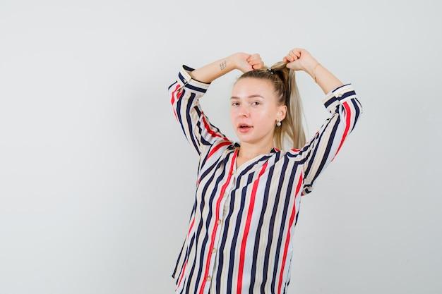 Junge dame, die beim ziehen des haares im gestreiften hemd aufwirft und stilvoll schaut