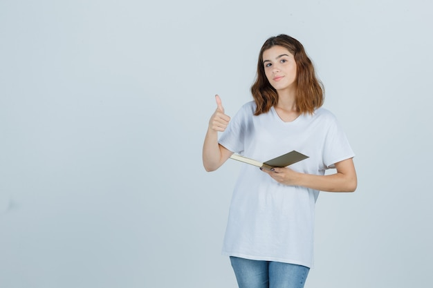 Junge dame, die buch hält, während daumen oben in t-shirt, jeans zeigt und glücklich schaut. vorderansicht.