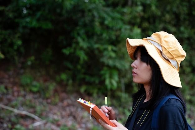 Junge dame, die buch in der hand hält, geologe und landvermesser, naturlehrpfad im nationalpark