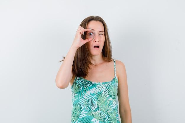 Junge dame, die das auge mit den fingern öffnet, um in der bluse klar zu sehen und fokussiert zu schauen, vorderansicht.