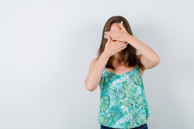 Junge dame, die das gesicht mit den händen in der bluse bedeckt und ernste, vorderansicht schaut.