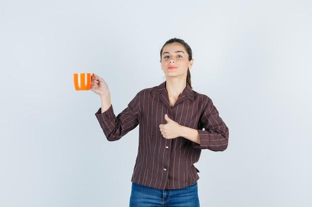 Junge dame, die daumen zeigt, tasse in hemd, jeans anhebt und selbstbewusst aussieht, vorderansicht.