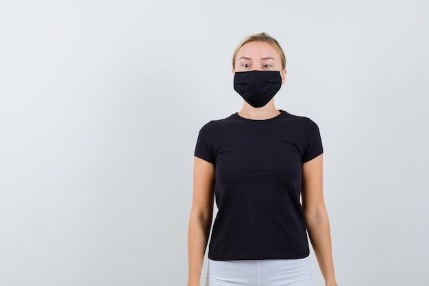 Junge dame, die die augen in t-shirt, hose, medizinischer maske zusammenkneift und lustig aussieht