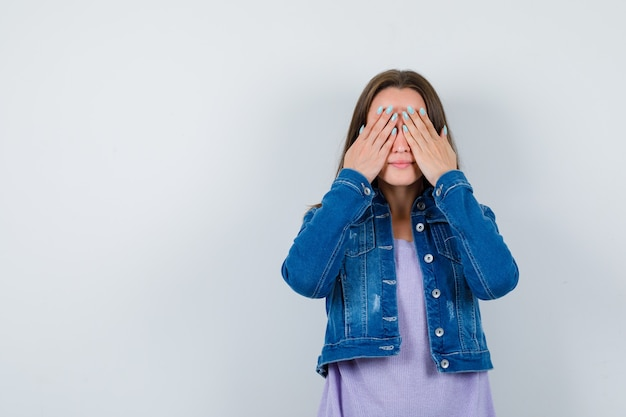Junge dame, die die augen mit den händen in t-shirt, jacke bedeckt und beschämt aussieht, vorderansicht.
