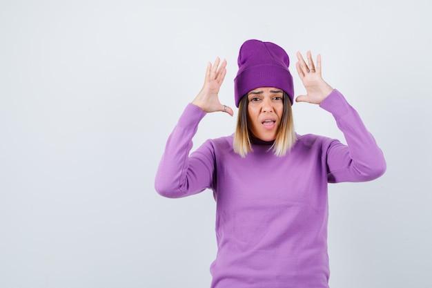 Junge dame, die die hände in der kapitulationsgeste in lila pullover, mütze hält und ängstlich aussieht, vorderansicht.