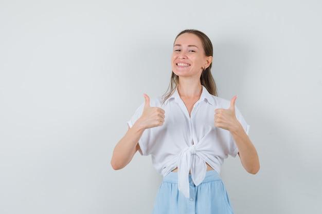 Junge dame, die doppelte daumen in bluse und rock zeigt und fröhlich aussieht
