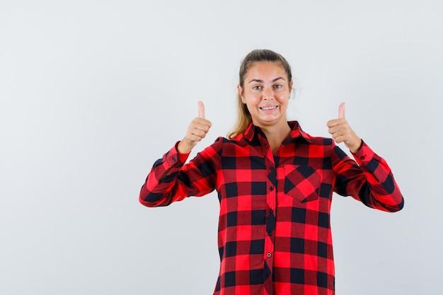 Junge dame, die doppelte daumen in kariertem hemd zeigt und selbstbewusst aussieht