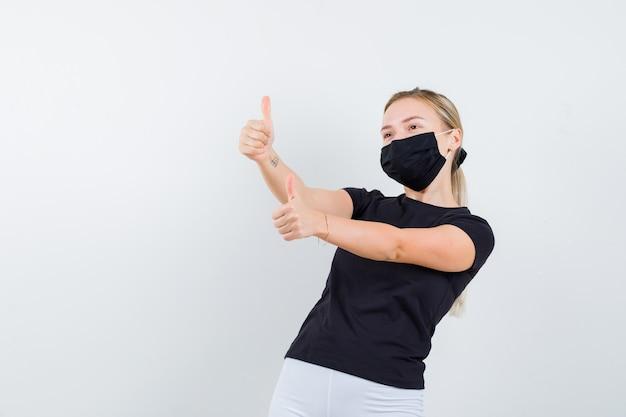 Junge dame, die doppelte daumen oben im schwarzen t-shirt, in der maske zeigt und glücklich schaut. vorderansicht.