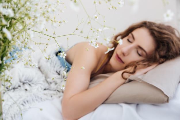 Junge dame, die drinnen im bett schläft. augen geschlossen.