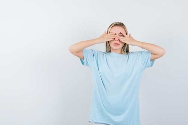 Junge dame, die durch die finger im t-shirt schaut und isoliert süß aussieht